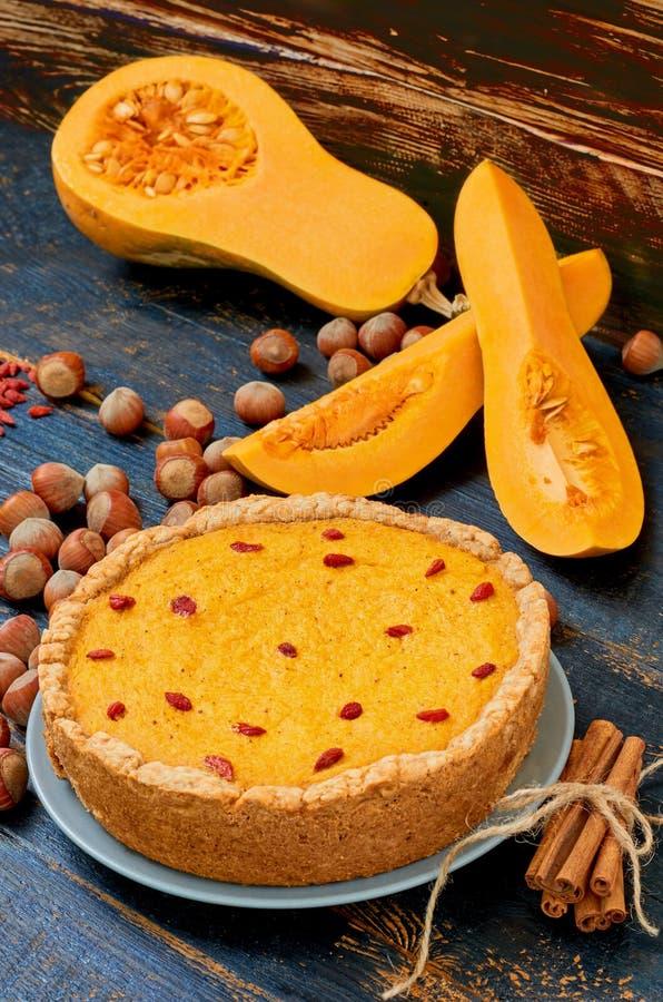 秋天馅饼用goji莓果装饰用榛子和桂香在黑土气木背景 传统点心的南瓜 库存照片