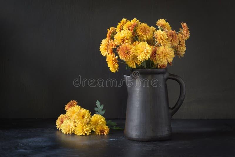 秋天黑暗静物画 落与在clayware花瓶的黄色菊花花在黑色 免版税库存图片