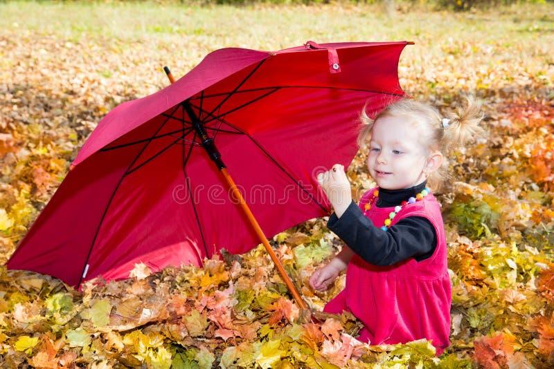 秋天 使用与下落的叶子的逗人喜爱的儿童女孩在秋天 免版税库存照片