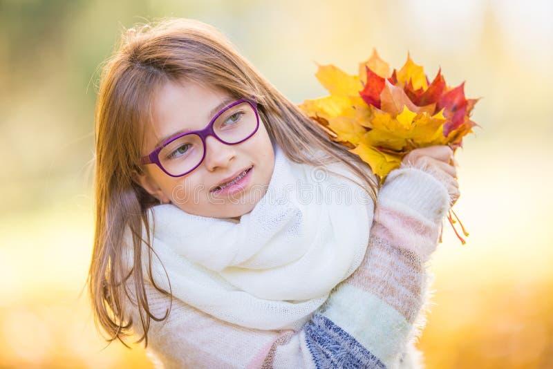 秋天 在她的手上拿着秋天槭树花束一个微笑的女孩的画象离开 库存照片