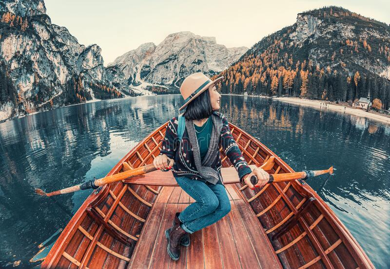 秋时,无畏的亚洲旅行者乘船在美丽的高山湖上航行 免版税库存图片