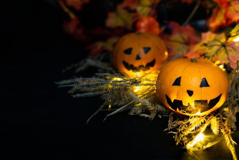 秋黄叶背景下,干草里两只有趣或生气的南瓜杰克灯头 一张张脸 免版税库存照片