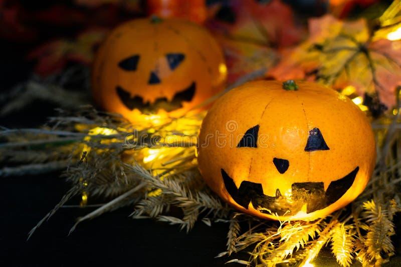 秋黄叶背景下,干草里两只有趣或生气的南瓜杰克灯头 一张张脸 免版税库存图片