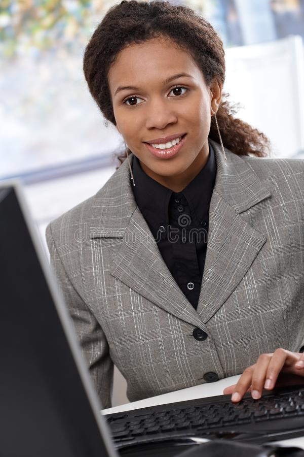 种族女实业家与计算机一起使用 免版税库存图片