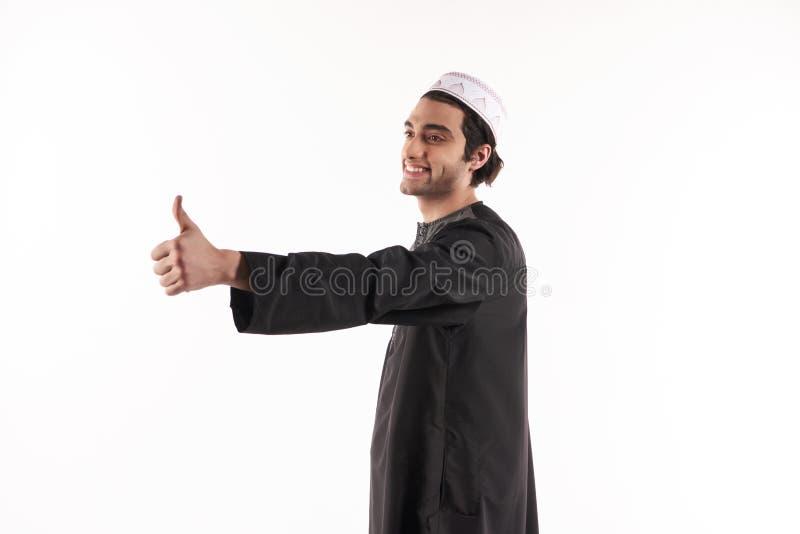种族衣裳的愉快的阿拉伯人显示赞许 库存照片