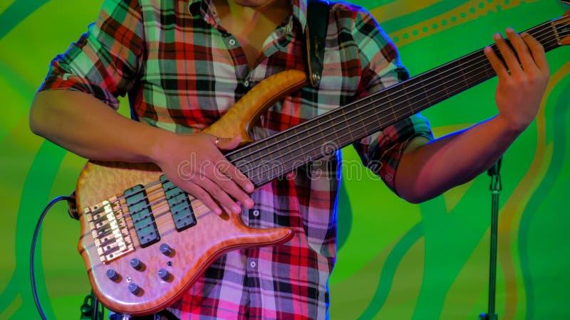 种族露天音乐会阶段的低音吉他球员  图库摄影