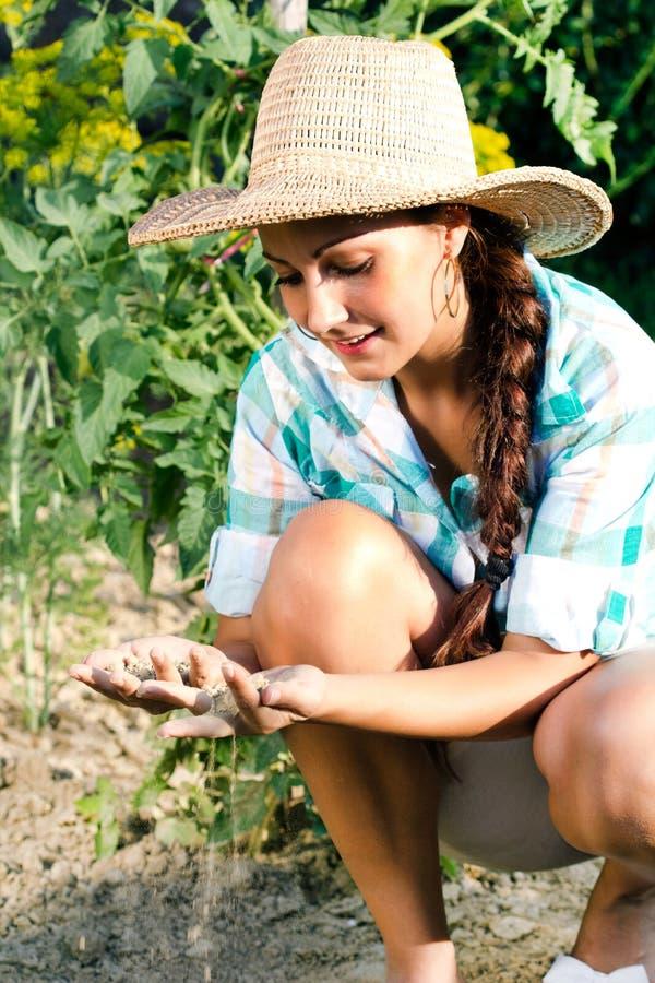 种植在庭院里的年轻美丽的妇女 免版税库存图片