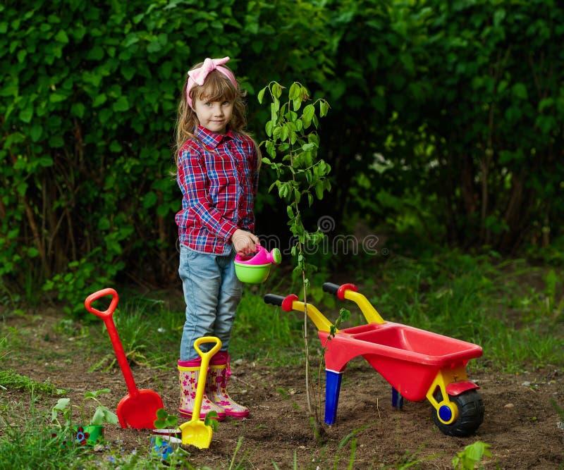 种植树的愉快的女孩 免版税库存照片