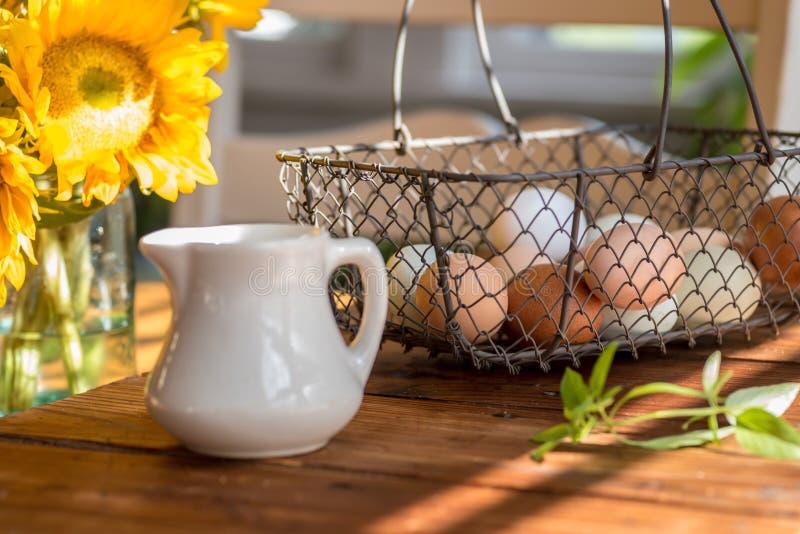 种田在一铁丝网筐的新鲜的鸡蛋在木桌面 免版税库存照片