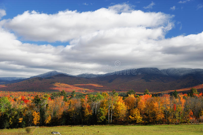 种田在与五颜六色的山和森林的秋季 免版税库存照片