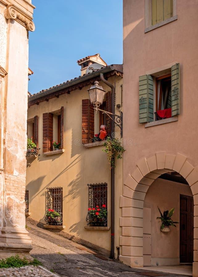 科内利亚诺,意大利- 2017年10月13日:一条小街道在科内利亚诺 与盲人的Windows用花装饰 的treadled 免版税图库摄影