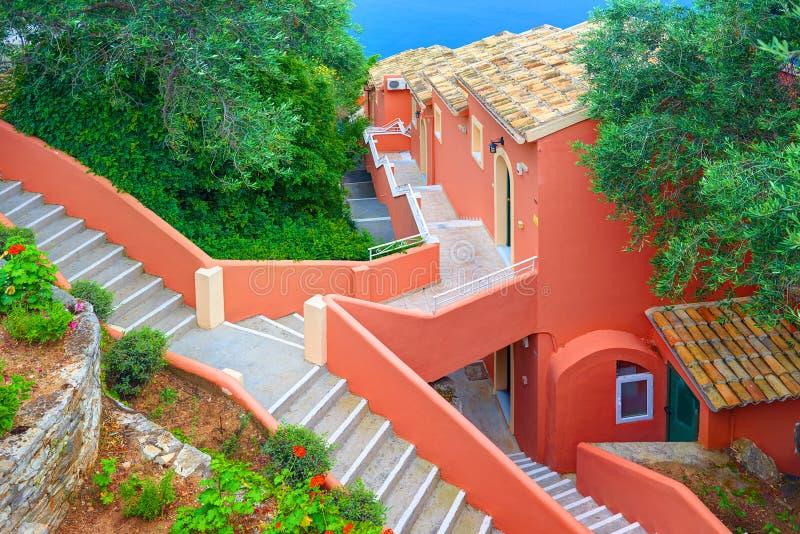 科孚岛海岛,希腊, 2014年6月03日:小瀑布红色黑暗玫瑰白色上色旅馆 希腊人开放石对角台阶楼梯 级联 库存图片