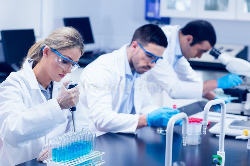 科学学生与化学制品一起使用在实验室 库存图片