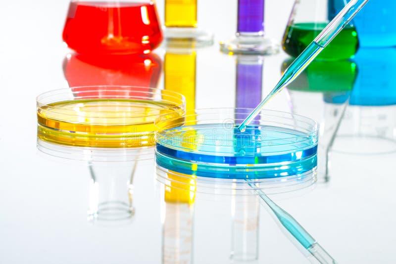 科学实验室玻璃器皿吸移管下落,反射性白色后面 免版税图库摄影
