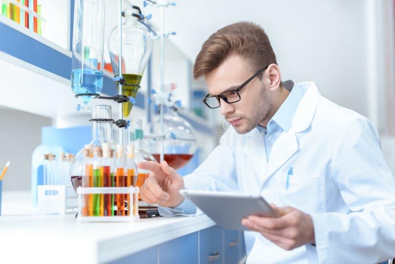 科学家拿着数字式片剂和与试管一起使用在实验室 免版税图库摄影