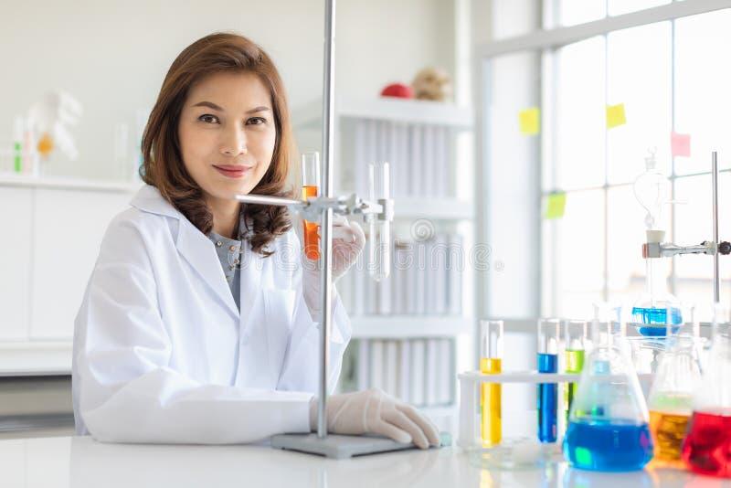 科学家拿着橙色试管的用途立场 免版税图库摄影