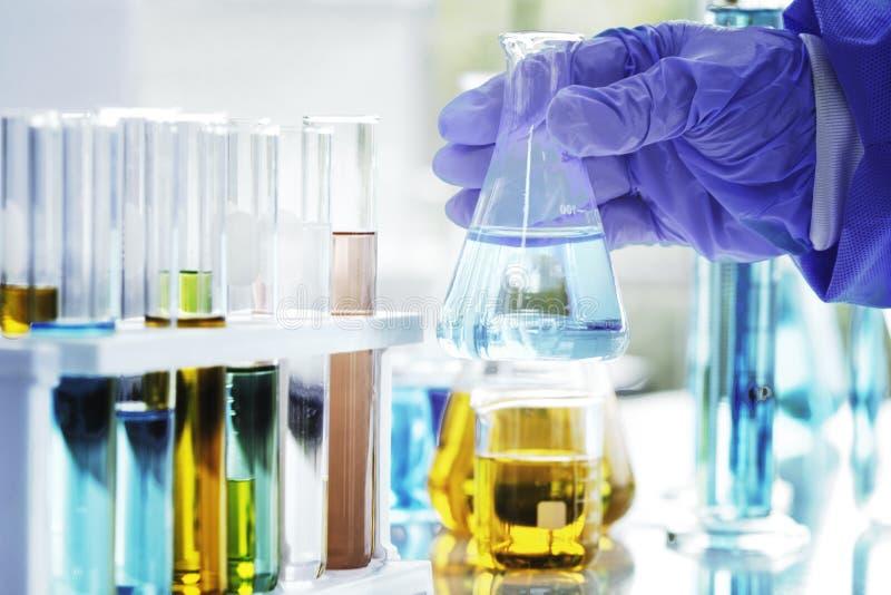 科学家是手拿着一个烧杯化学制品在实验室里 库存照片