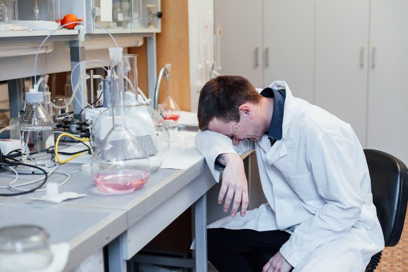 科学家睡觉在工作在实验室里 免版税库存图片