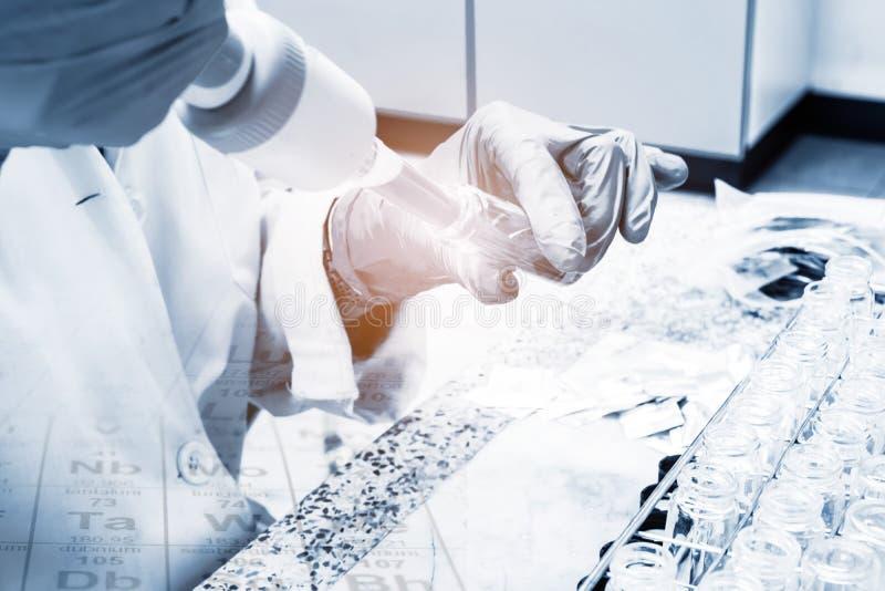 科学家积土化学制品到试管、设备和科学里试验 免版税库存照片