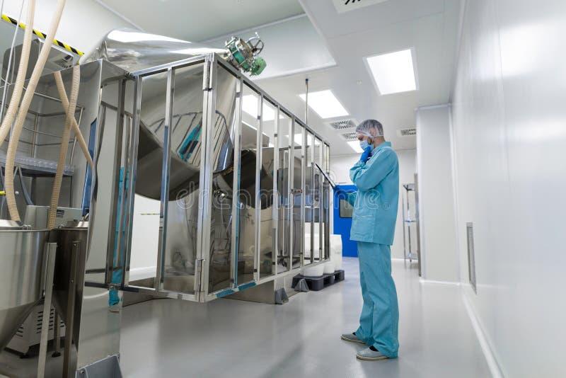 科学家立场近被镀铬的桶 免版税库存图片