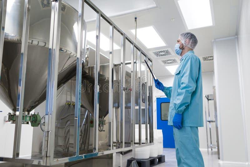 科学家立场近被镀铬的桶 免版税库存照片
