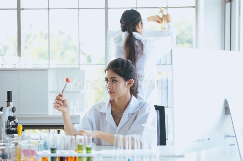 科学家美丽的亚裔妇女与切片检查法样品一起使用在实验室 图库摄影
