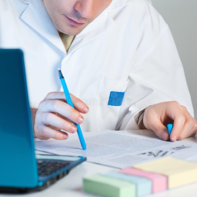 年轻科学家读新出版物 免版税图库摄影