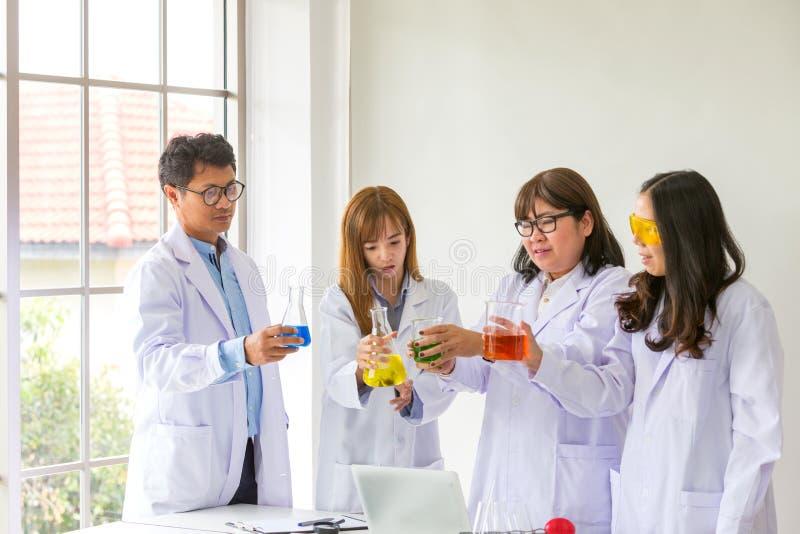 科学测试化学家科学测试的质量 工作在实验室的小组科学家 一名男人和三妇女化学实验室的 库存图片