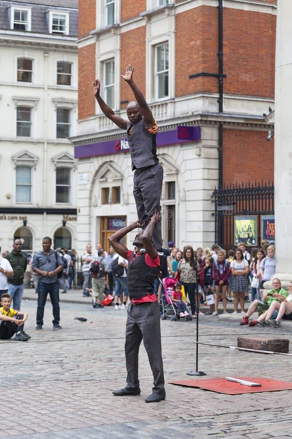 科文特花园市场、普遍的购物和旅游胜地,在街道,伦敦,英国上的黑人马戏团演员 库存图片