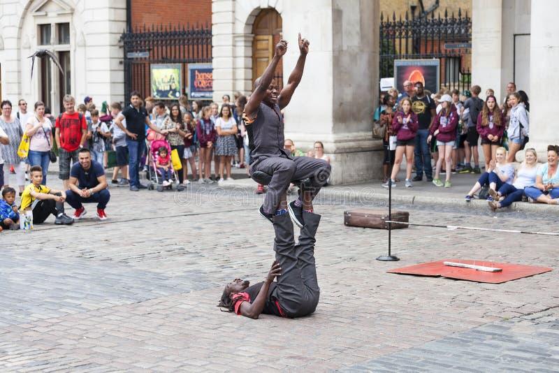 科文特花园市场、普遍的购物和旅游胜地,黑人马戏团演员展示在街道,伦敦,英国上的 库存图片