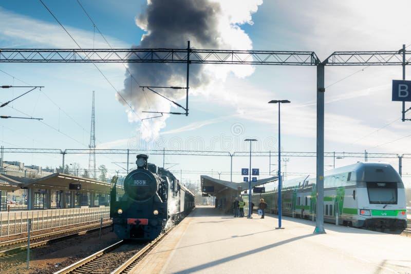 科沃拉,芬兰- 2019年4月18日:现代两列的火车老和在驻地在早晨 老蒸汽火车Ukko佩卡离开 免版税图库摄影