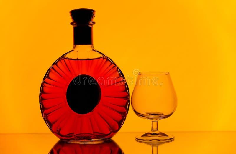 科涅克白兰地瓶和一口威士忌酒玻璃反对金黄黄色背景 库存图片