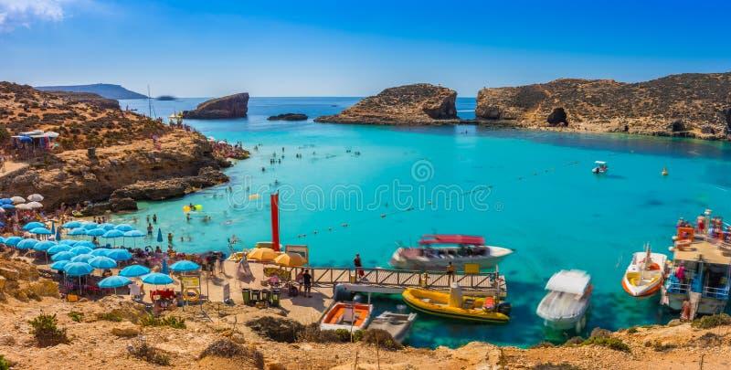 科米诺岛,马耳他-游人在蓝色盐水湖拥挤享用清楚的绿松石水 图库摄影