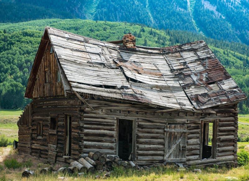 科罗拉多先驱在有顶饰小山附近的原木小屋 免版税库存照片