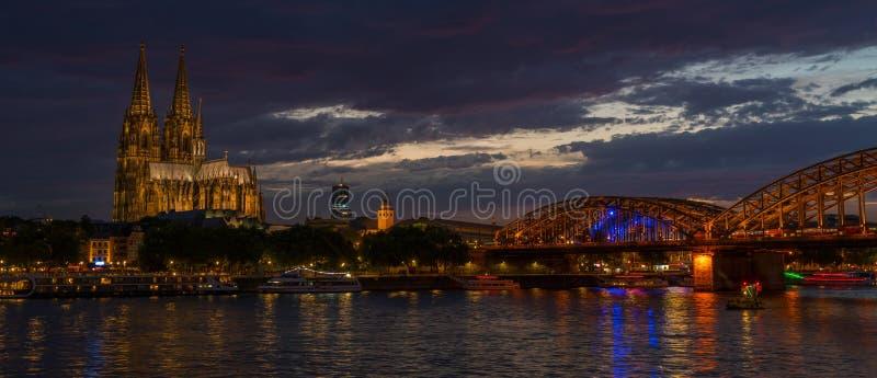 科隆主教座堂和霍亨索伦桥梁在河莱茵河,德国的晚上 免版税库存图片