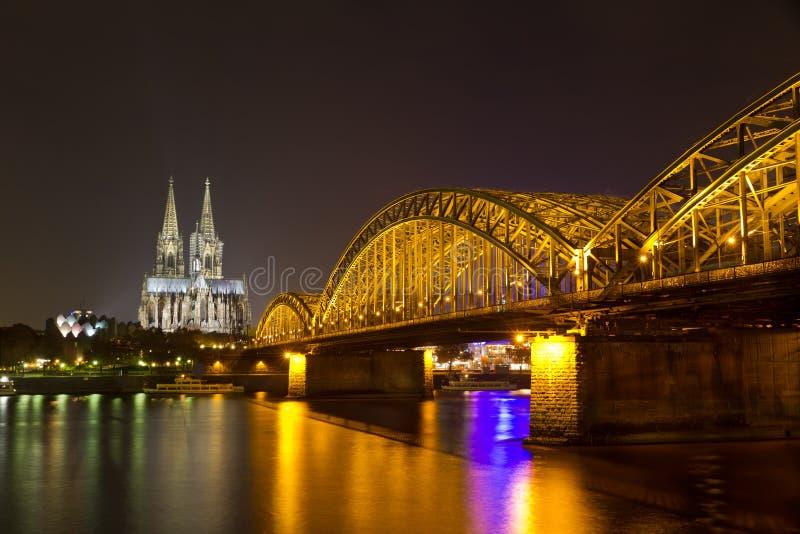 科隆大教堂和Hohenzollern桥梁在晚上,科隆(Koeln),德国 免版税库存图片
