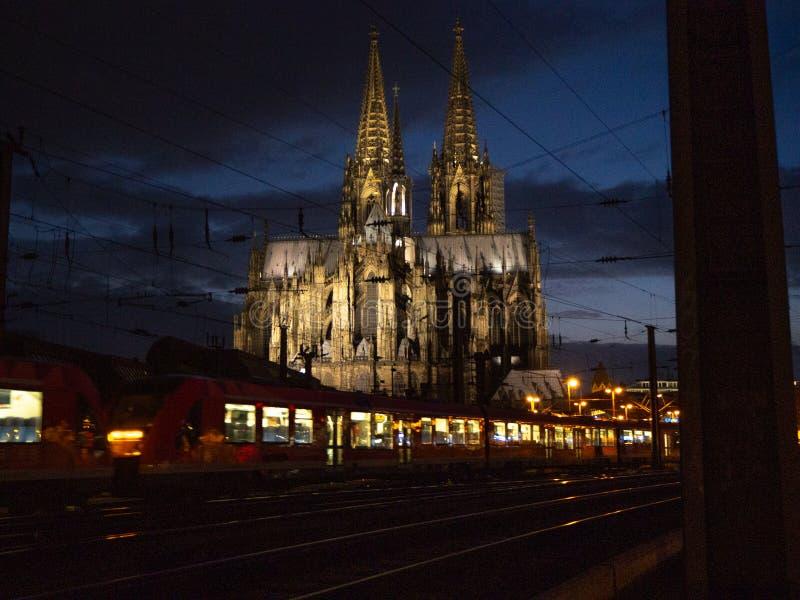 科隆大教堂在与通过通过的火车的晚上 图库摄影