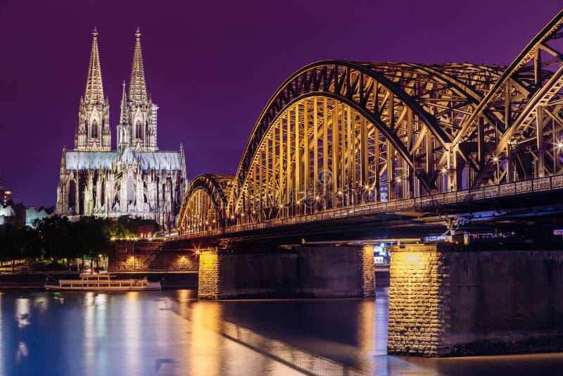 科隆香水德国 科隆大教堂和Hohenzollern桥梁夜视图  免版税库存照片