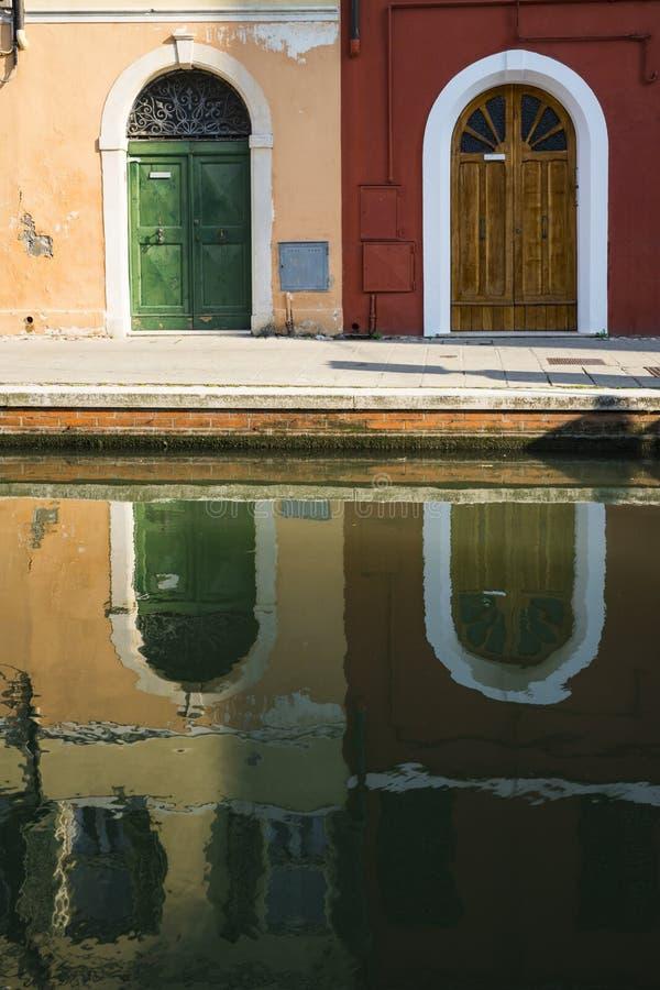 科马基奥,意大利运河的反射橙色和红色房子  免版税库存图片