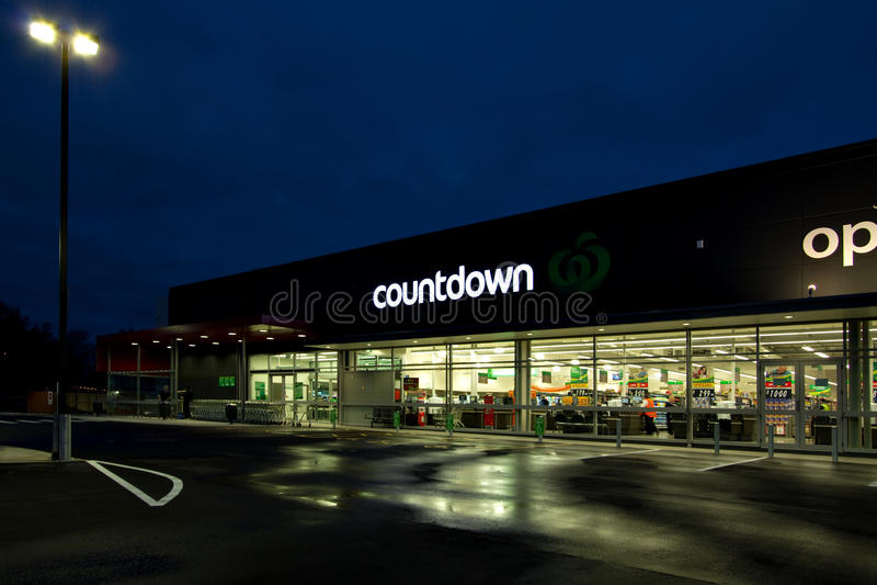 读秒杂货超级市场在多雨夜打开了 免版税库存图片