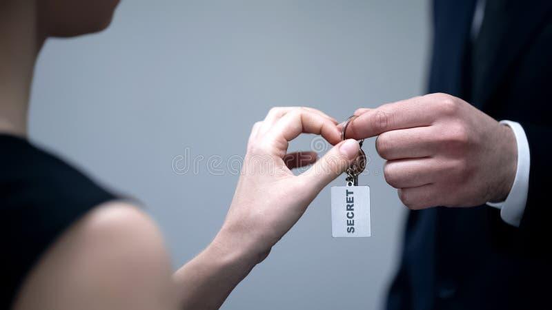 秘密信息,安全限界,数据泄漏的男性给的妇女钥匙 库存图片