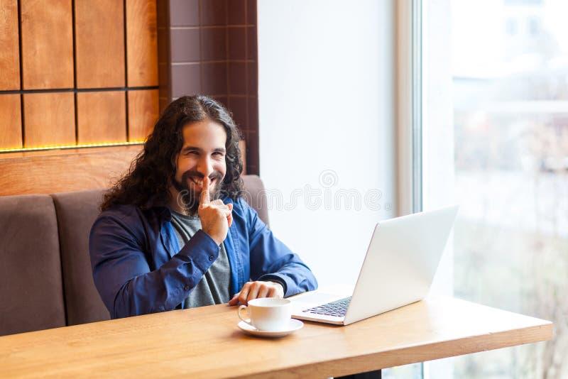 秘密!愉快的英俊的坐在与膝上型计算机和显示的咖啡馆的便装样式的智力年轻成人人自由职业者画象  库存图片