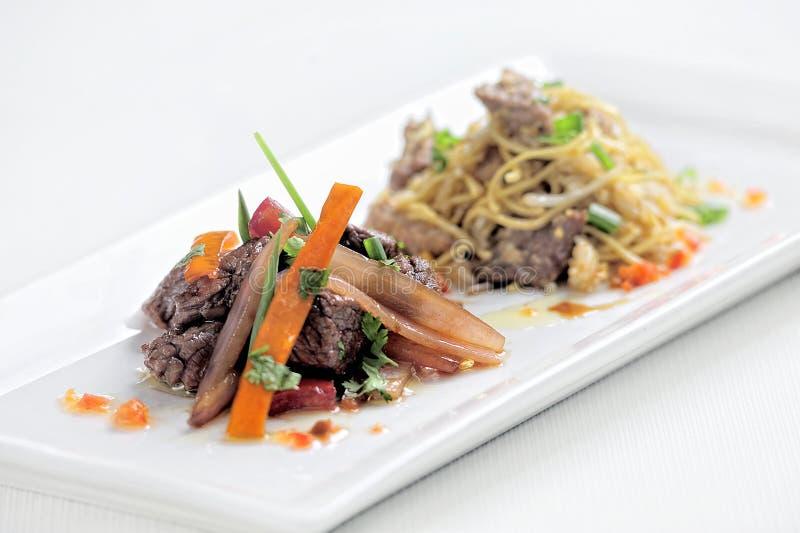 秘鲁盘称Lomo Saltado由蕃茄、与炸薯条和葱做成混合的牛肉肉 免版税库存照片