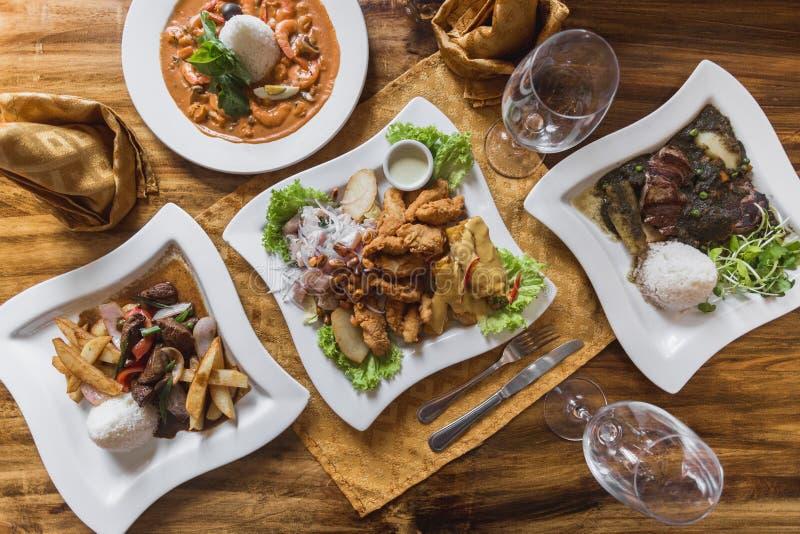 秘鲁食物,ceviche,lomo saltado,在一张典雅的餐馆桌上的piqueo 免版税库存照片