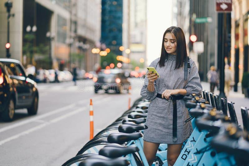 租用从自行车立场的女孩一辆城市自行车 库存照片