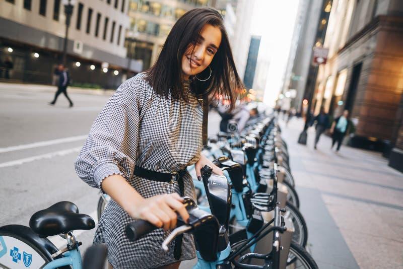 租用从自行车立场的女孩一辆城市自行车 图库摄影