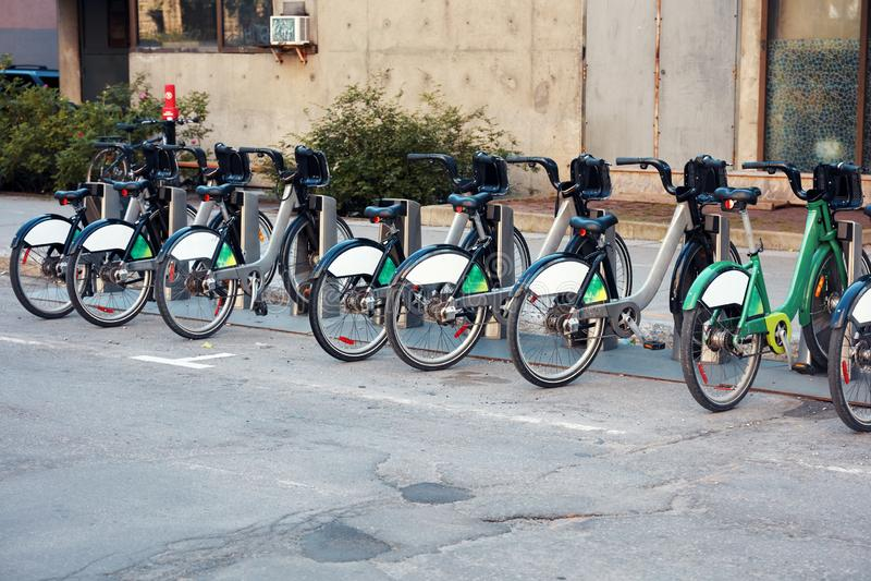 租的绿色城市自行车在都市自行车出租驻地 免版税库存图片