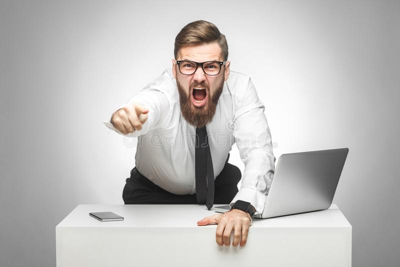 积极的不快乐的年轻商人画象在白色衬衫的和半正式礼服在办公室责备您并且有心情, 免版税库存照片