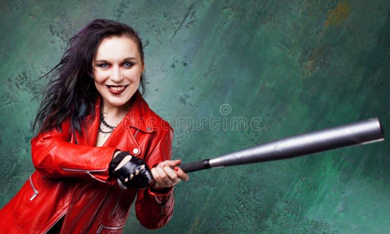 积极的低劣的妇女罢工某人有一根棒的,在红色皮夹克 库存图片
