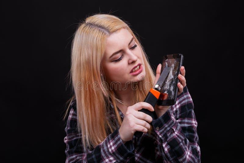积极的女孩,裁减残破的智能手机屏幕使用建筑刀子的 黑色背景 图库摄影